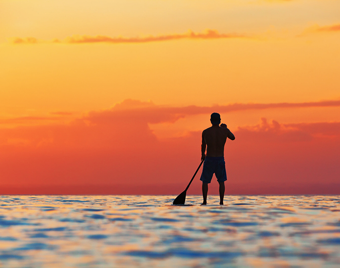 Paddle boarder. Black sunset silhouette of young sportsman paddling on stand up paddleboard.